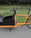 Oranje bakfiets Bullitt, zitje, zijpanelen, zeil, bagagerek