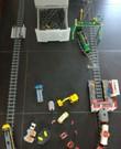 Twee opgebouwde Lego treinensets met station en extra rails in opbergtoren